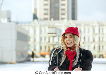 Wonderful smiling blonde woman wearing trendy cap having fun with sparklers at the street. Space for text