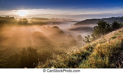Wonderful sunrise at foggy valley in autumn