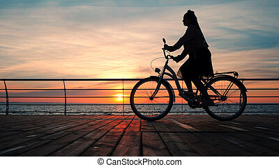 Wonderful sunrise or sunset above ocean. Silhouette of young stylish girl cycling on vintage bike on wooden embankment. Woman on bicycle near sea.