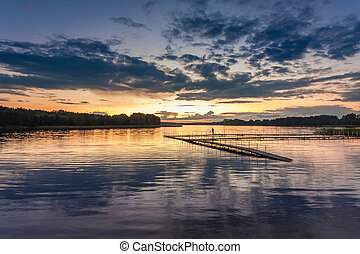 Wonderful sunset at the lake with dynamic sky in summer