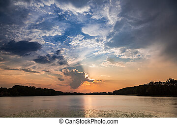 Wonderful sunset at the summer lake with dynamic clouds