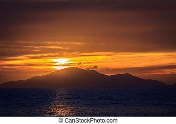 Wonderful sunset behind mountains peak protruding from...