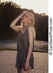 Wonderful tanned blonde girl with long hair wearing black romper, posing in sun glare