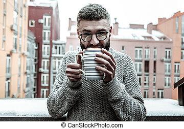 Nice good looking man enjoying his warm drink
