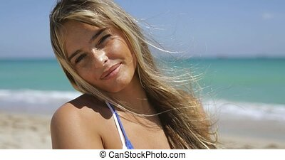 Wonderful woman smiling in sunshine on beach - Headshot of...