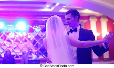 Wonderful young couple in love dancing their first valse in a restaurant.