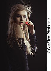Wonderful young model with long blonde hair posing in the shadows
