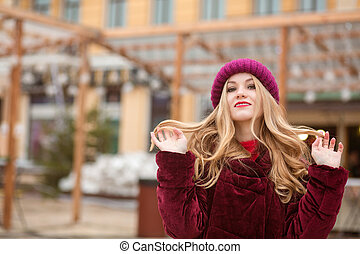 Wonderful young woman with long hair posing at the street in Kiev