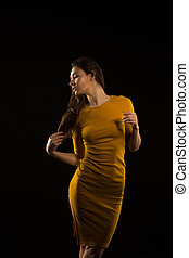 Wonderful young woman with long hair posing in yellow dress in the shadow