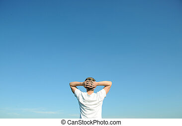 Young man in white t-shirt looking at the blue sky. Above space for text or graphics.