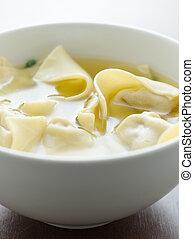 Wonton soup in a white bowl.
