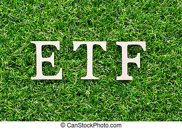 Wood alphabet in word ETF (abbreviation of Exchange Traded Fund) on artificial green grass background