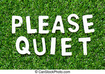 Wood alphabet letter in word please quiet on green grass background