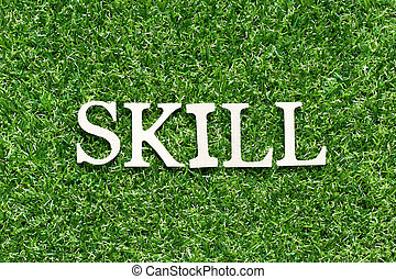 Wood alphabet letter in word skill on artificial green grass background