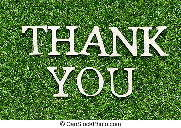 Wood alphabet letter in word thank you on artificial green grass background