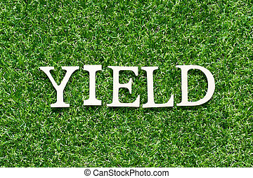 Wood alphabet letter in word yield on artificial green grass background
