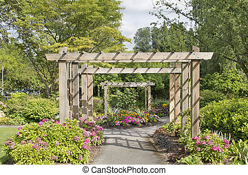 Wood Arbor Over Garden Path with Plants Trees and Flowers...