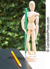 Wood artist mannequin standing with colour pencil