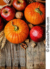 wood background with pumpkin, apples, wheat, honey and nuts