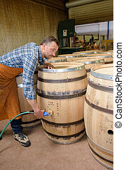 wood barrels production cooper using hammer and tools in...