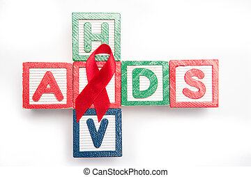 Wood blocks spelling aids and HIV in a cross shape with red...