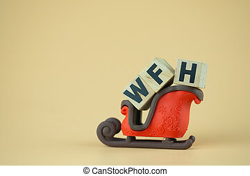 Wood blocks word of WFH on a santa claus sleigh toy.
