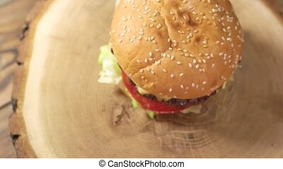 Wood board with burger. Top view of tasty cheeseburger.