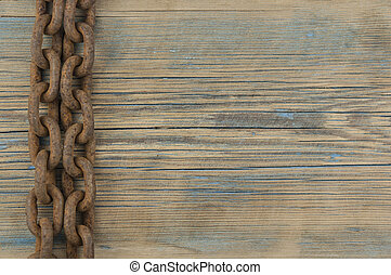 Wood board with iron chain link. Rusted chain hanging in front of a wood background. Industrial detailed object. Steel chain.