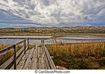wood boardwalk leading to a saline. HDR picture.