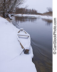Wood boat covered with snow on shore of winter river