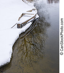 Wood boat covered with snow on the shore of winter river