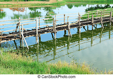 Old unfinished wood bridge over water in a garden