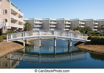Wood Bridge Over Blue Lagoon in Luxury Condo Complex