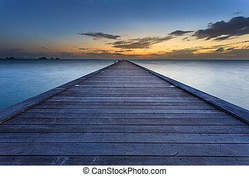 Wood bridge to the sea at sunset beach in Koh Samui, Thailand