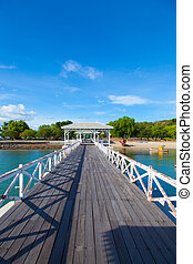 Wooden bridge stretching into the sea. Small boats moored nearby.
