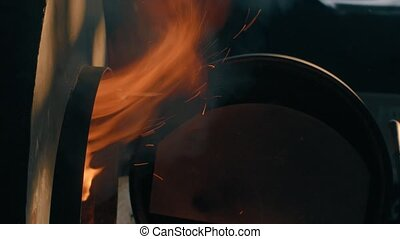 Wood burning in the stove. Flame comes out of the stove