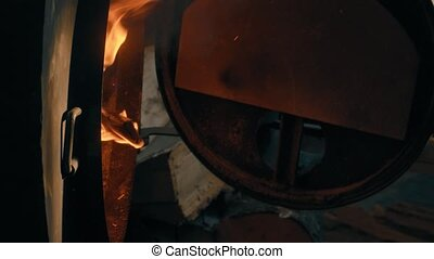 Wood burning in the stove. Man's hand closing a door of a stove and locking it.