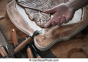 Wood carving, hand of a craftsman for the tool,