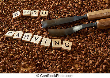 wood carving word writen with letters on wood chips and chisels