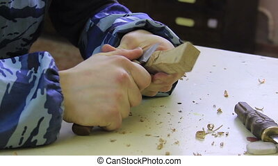 Wood Carving - Young man cutting wood for the handle of the...
