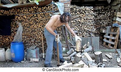 Wood chopping - shirtless man chopping wood