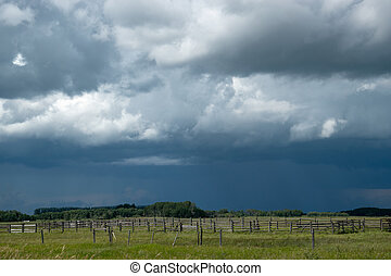 Wood Corral with approaching storm clouds, Saskatchewan, Canada.