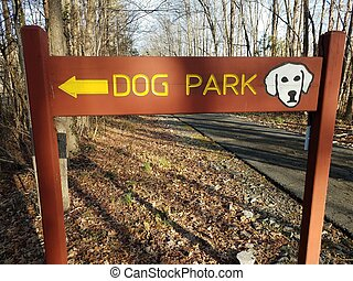 wood dog park sign with yellow arrow and asphalt trail and trees