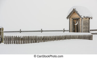 Wood fence leads to a snow covered outhouse - Cold winter...