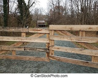 wood fence or gate and gravel road to house