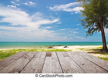 Wood floor top on blurred blue sea and white sand beach