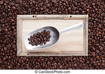 wood frame with scoop on top of flat lay of brown roasted coffee bean can be used as a background