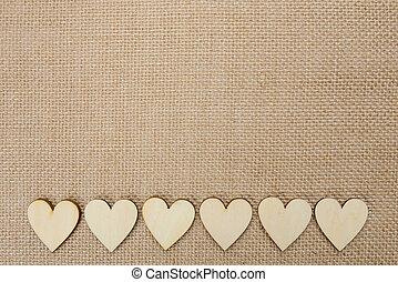 Wood hearts on hessian texture background, valentine...