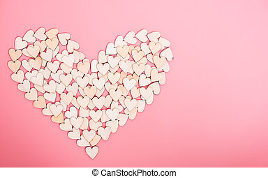 Wood hearts on pink background
