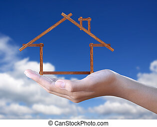 wood house in hand on blue sky